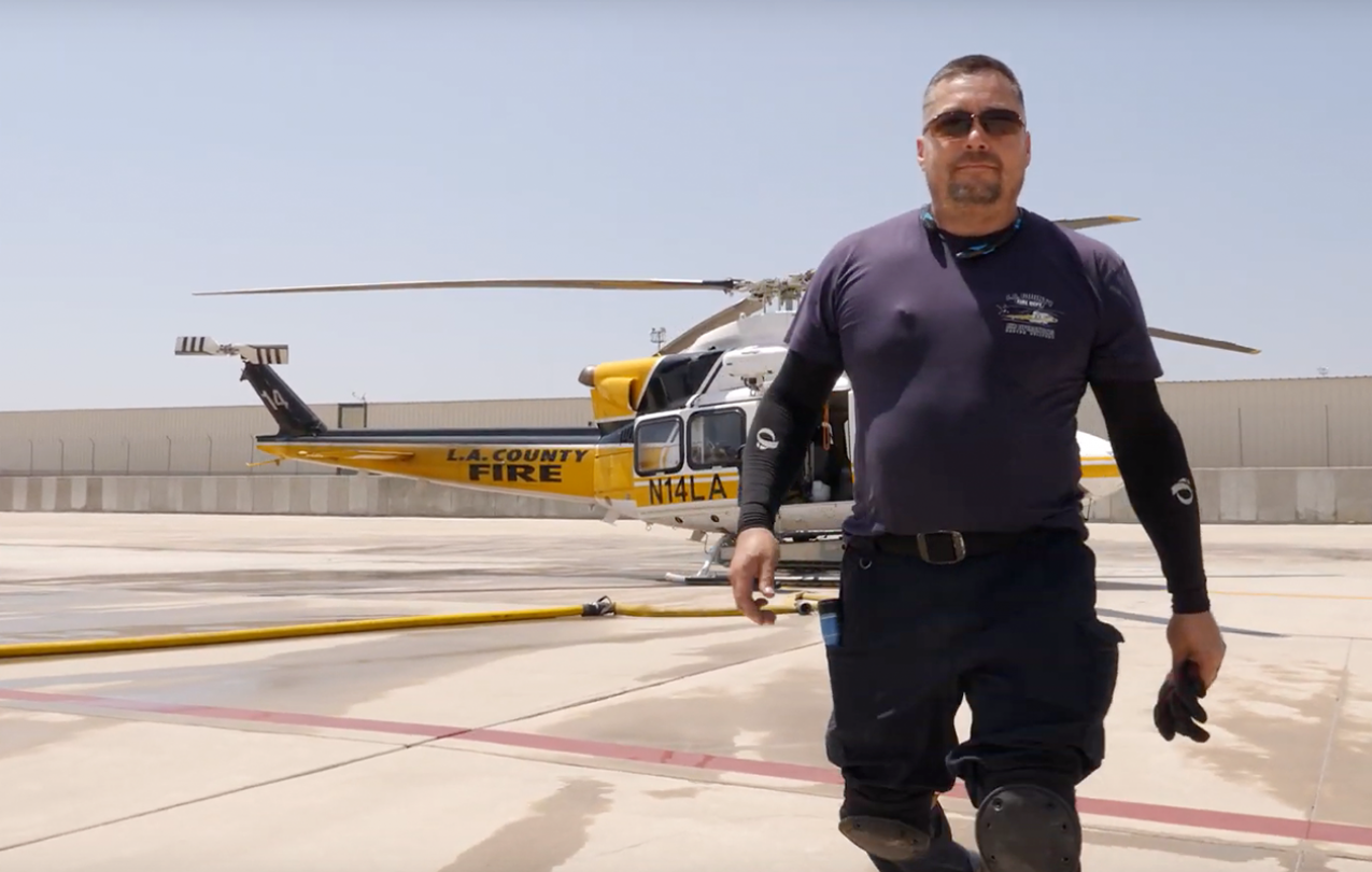 Joe Martinez poses in front of an LA County Fire Department helicopter.